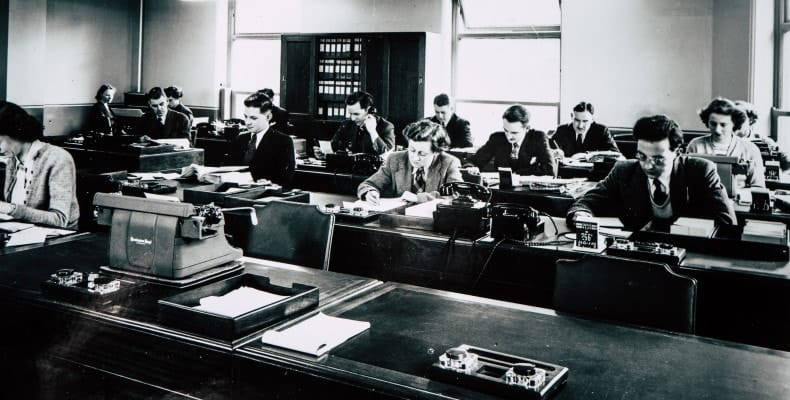 Accounting workers in an early 20th century office (black & white)