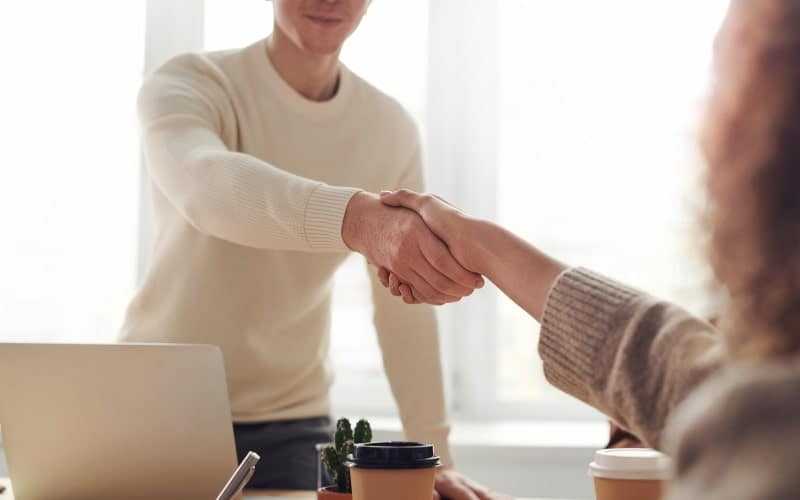 Standing make reaches across desk to shake woman's hand