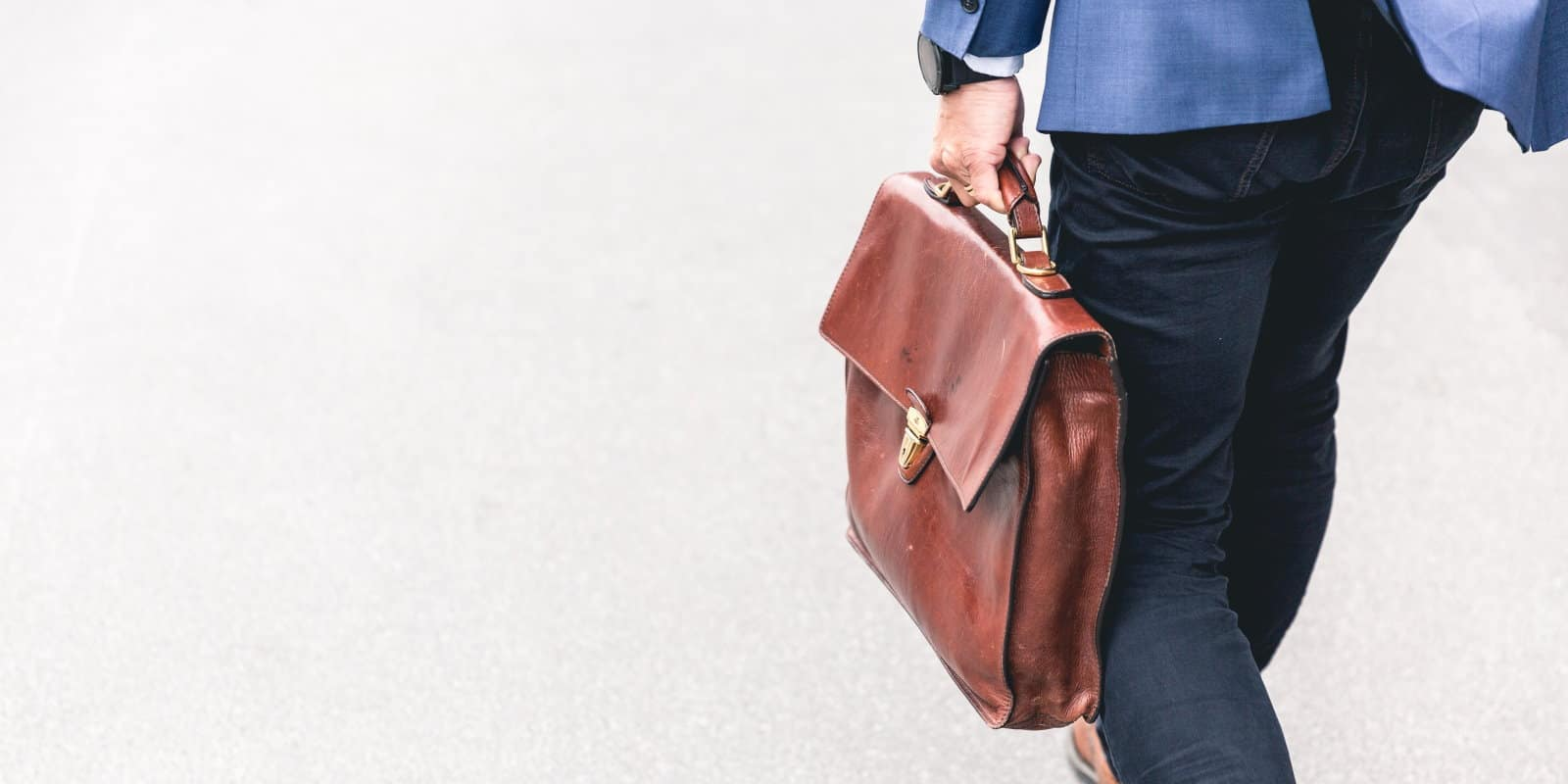 Man in jeans walks away from camera carrying a worn brown leather briefcase
