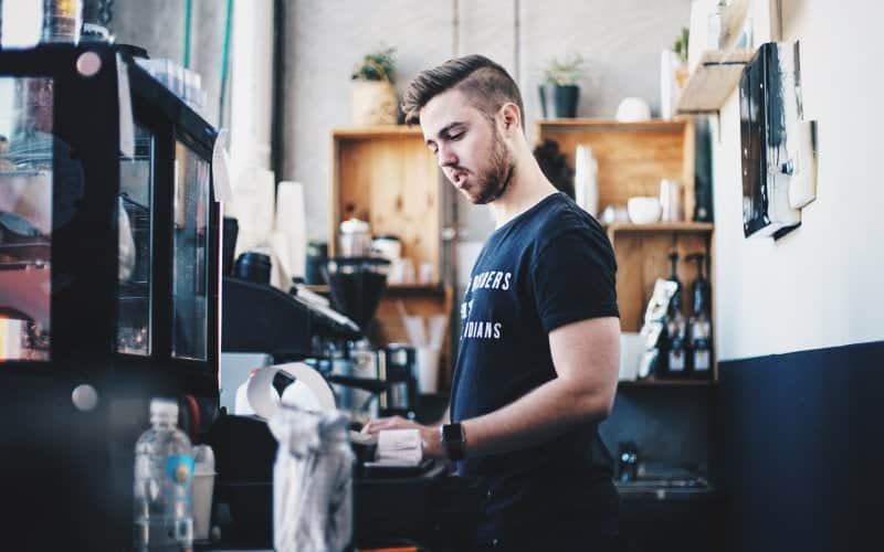 A barista working in a cafe pours coffee