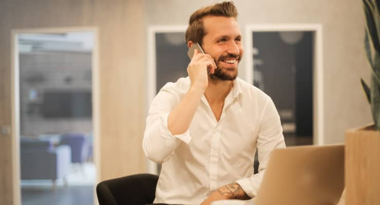 A smiling businessman with a beard dressed in a white shirt talks on a smartphone