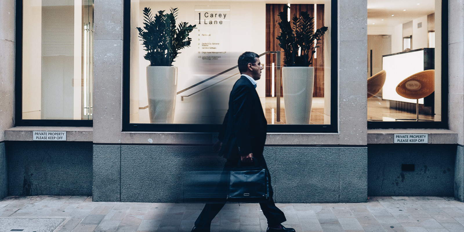 A businessman walking on the street past the windows of an office reception area