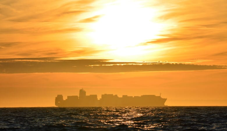 A container ship silhouetted on the horizon at sunset