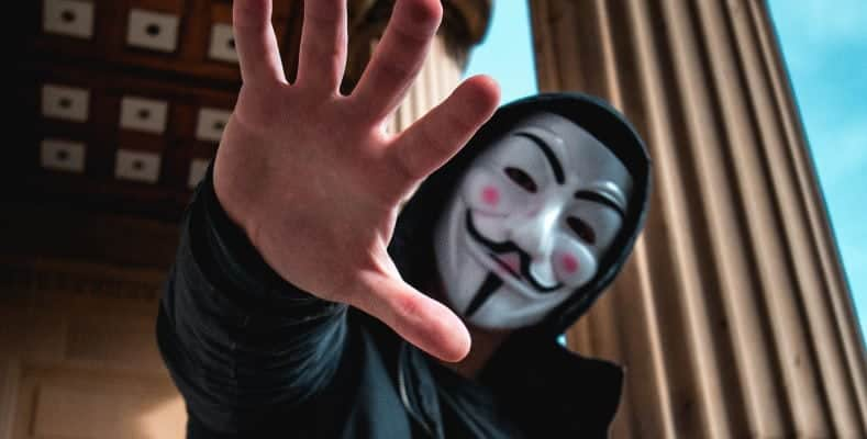 A man wearing a Guy Fawkes mask usually associated with the hacker group Anonymouskers