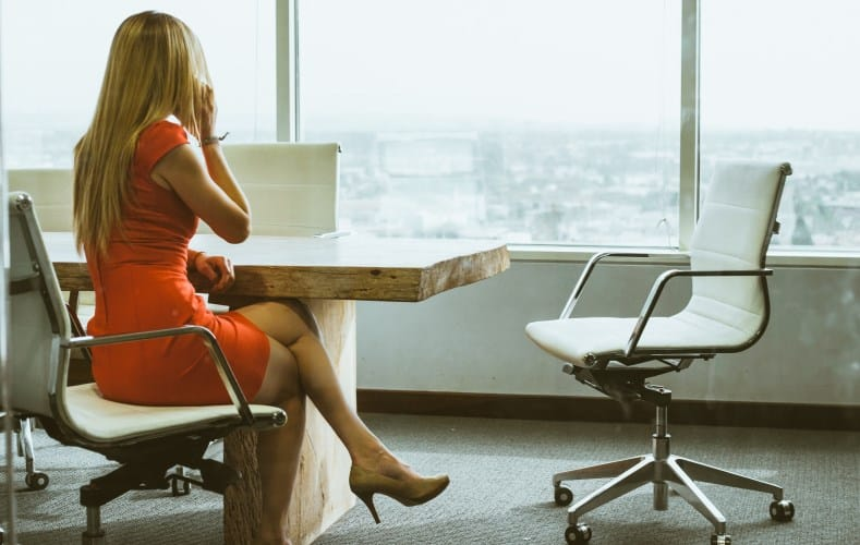 Businesswoman in an orange dress sitting at a boardroom table