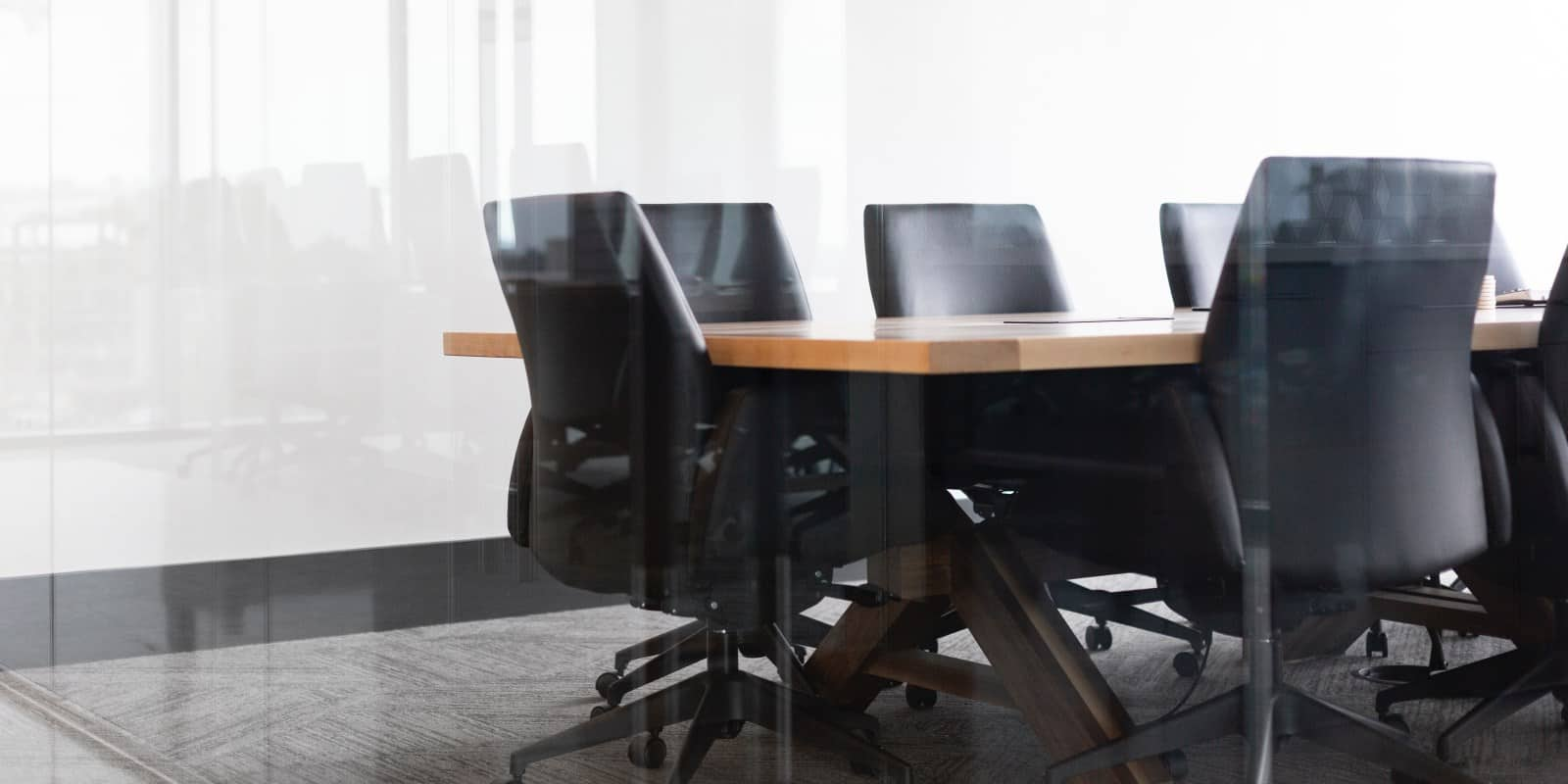 Black leather directors chairs around a boardroom table