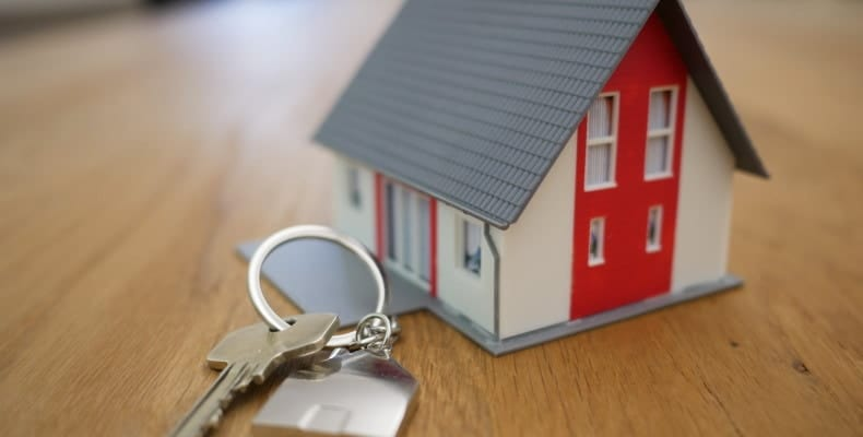 Keys sitting on a table, keyfob attached featuring a small house with grey slanted roof and a red door