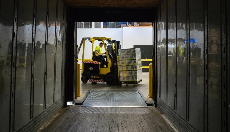 View looking out from the inside of a freight truck as a forklift loads a pallet of goods