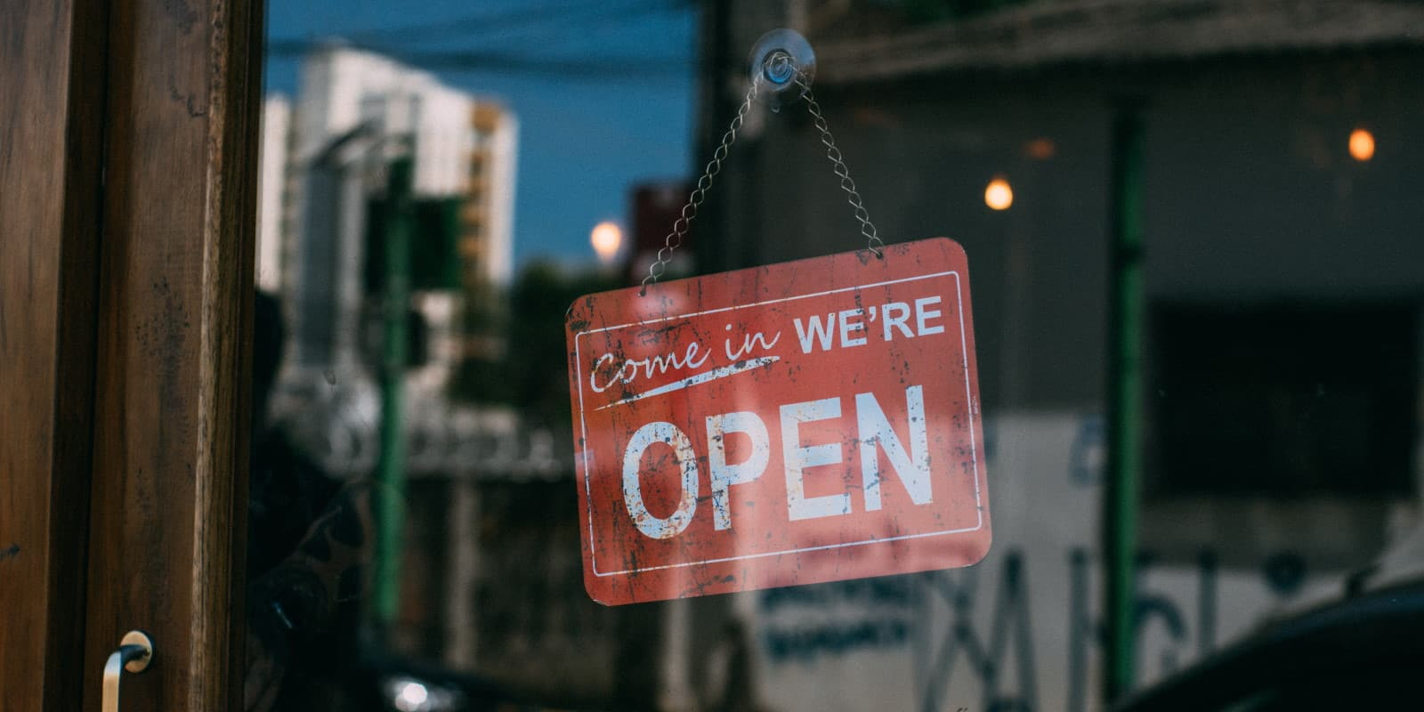 We're open sign hanging in a shopfront window