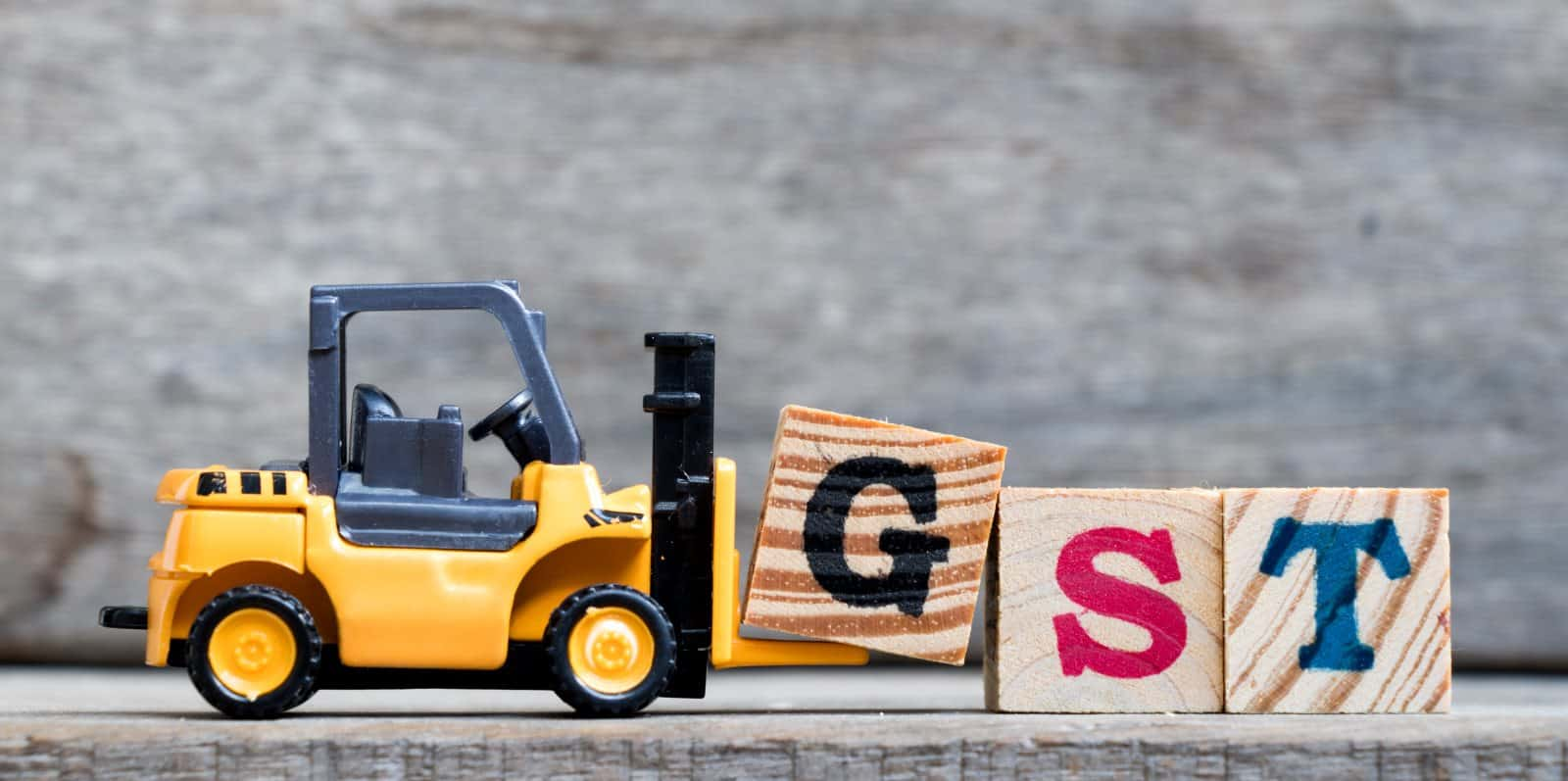 Yellow plastic forklift hold letter G to complete word GST (Abbreviation of Goods and Services Tax) on wood background