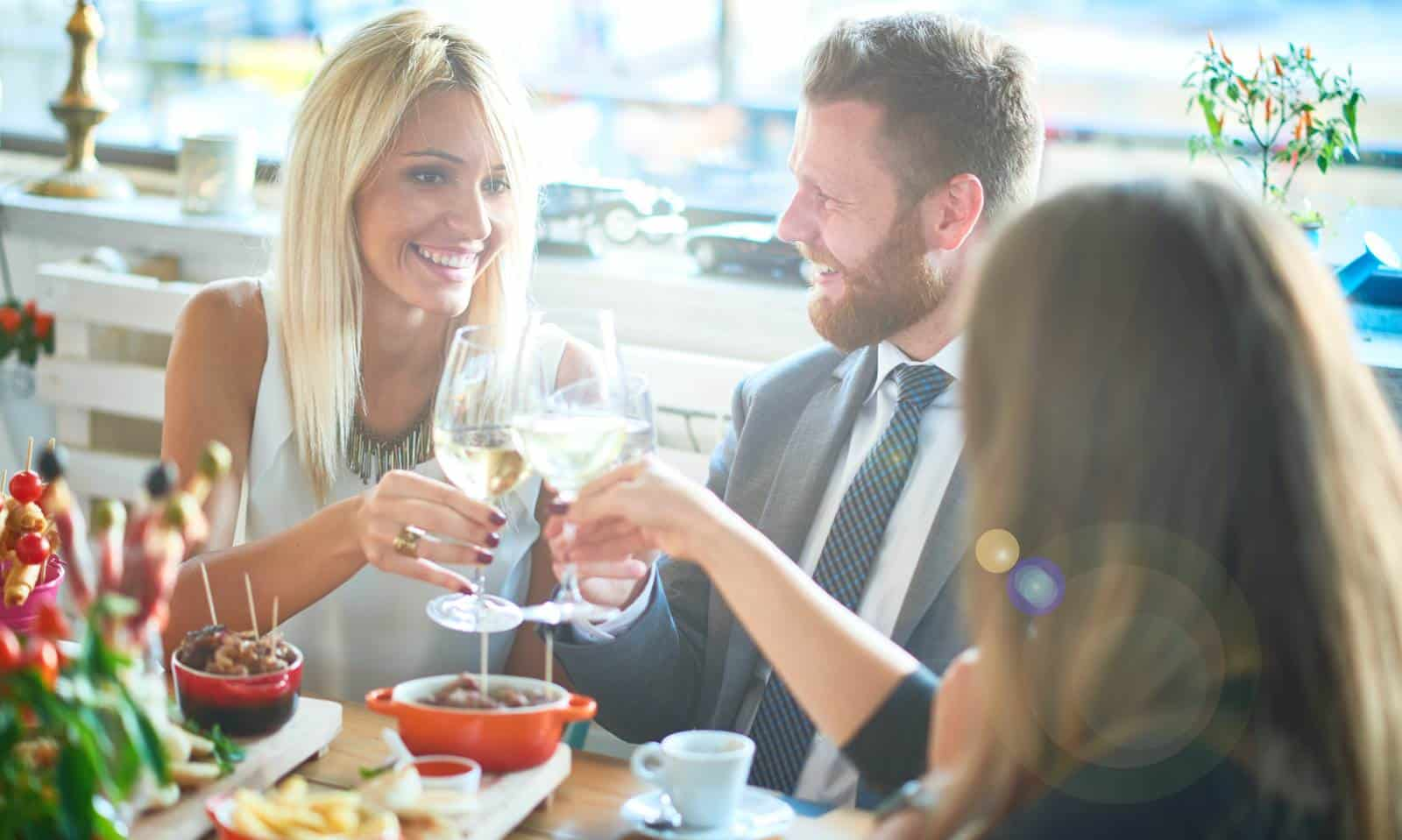 Business people enjoy a restaurant meal that may incur fringe benefits tax for their employer