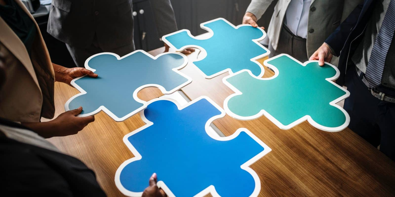 Group of business professionals with large puzzle pieces