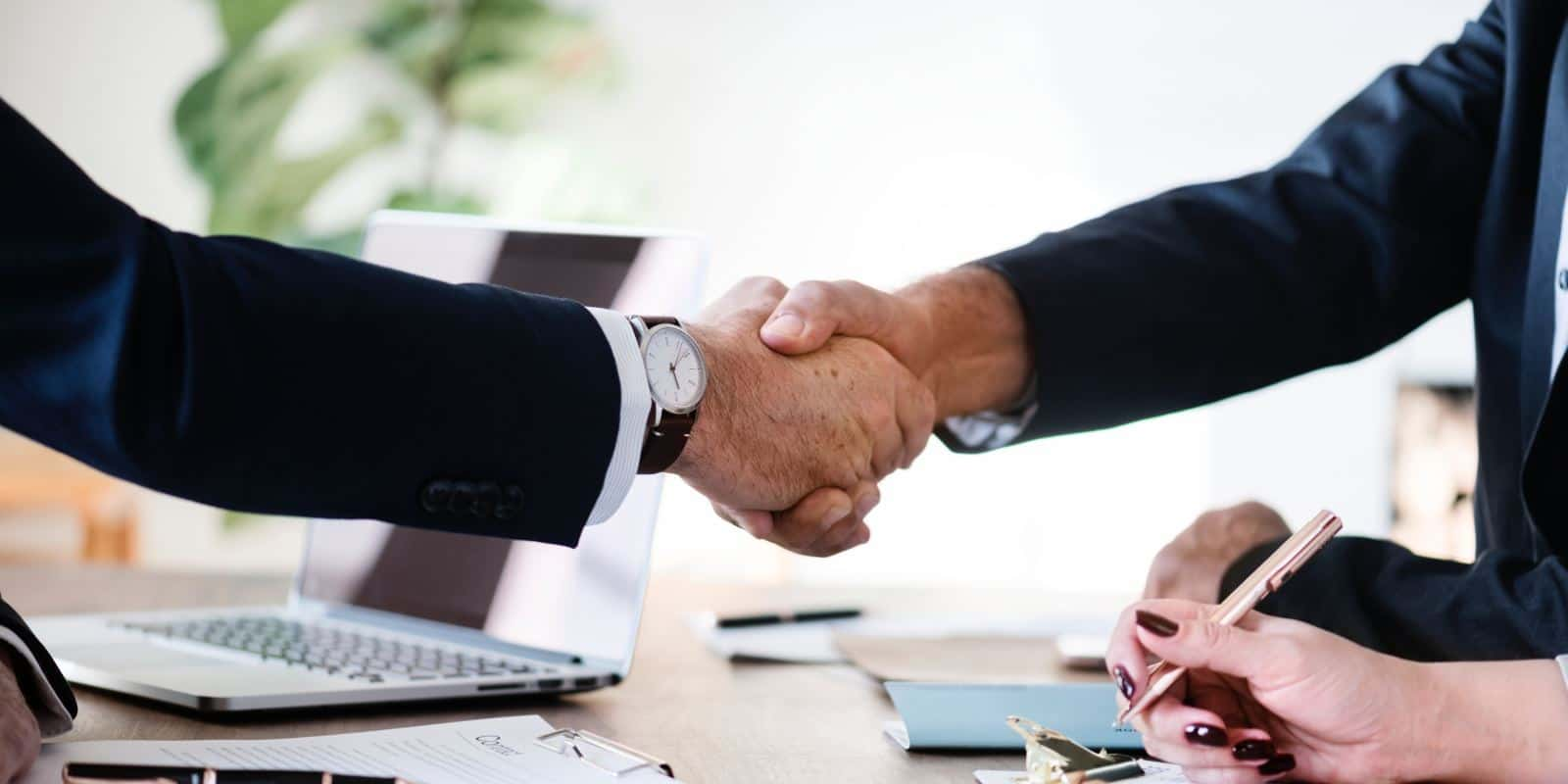 2 business people shaking hands over a meeting table