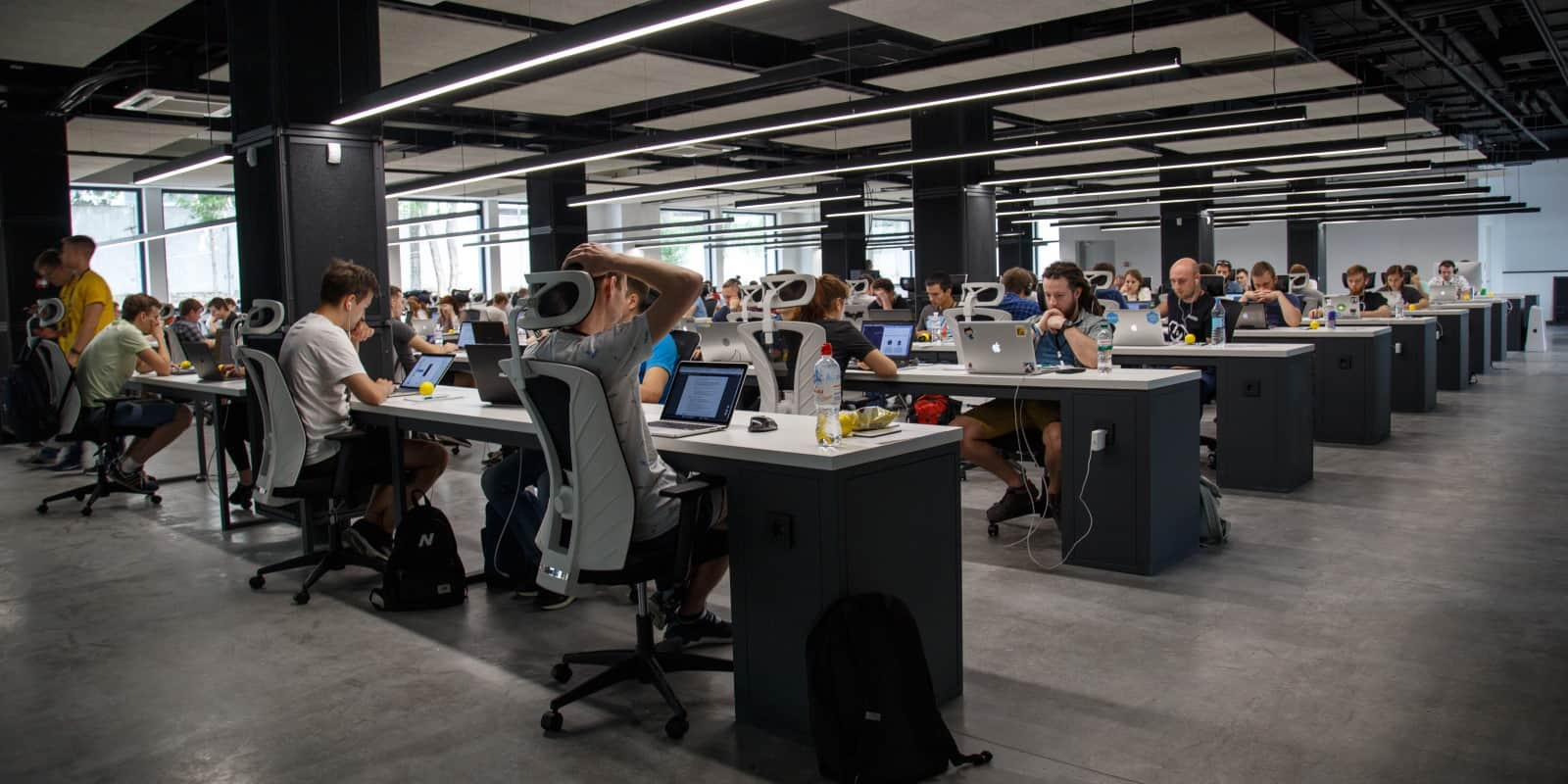 Rows of desks & computer workers in the office of a startup company